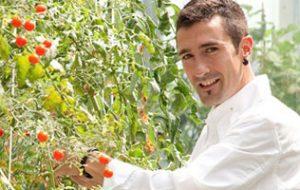 foto del chef Eneko Atxa con una planta de tomatescherrys.