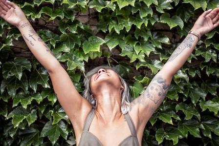 chica con los brazos en alto delante de un muro con plantas verdes.