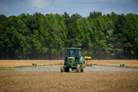 tractor echando plaguicidas en un campo