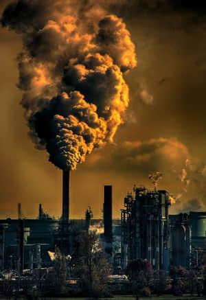 empresa con chimenea enorme echando humo contaminante
